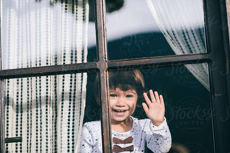 Cute little girl waving from the window by Adrian Cotiga for Stocksy United