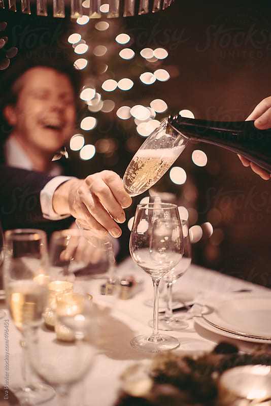 Serving champagne in a cozy christmas dinner with family and friends. by Eva Plevier for Stocksy United