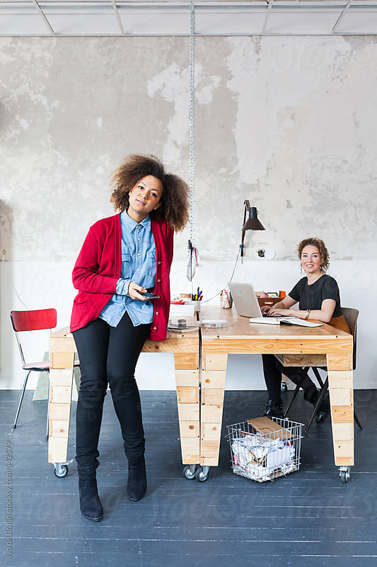 Photo of a small creative business team consisting of two women working in their office by Ivo de Bruijn for Stocksy United