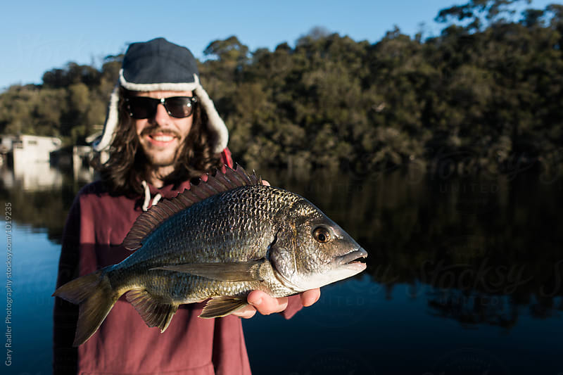 Young Man holding a Southern Black Bream by Gary Radler Photography for Stocksy United
