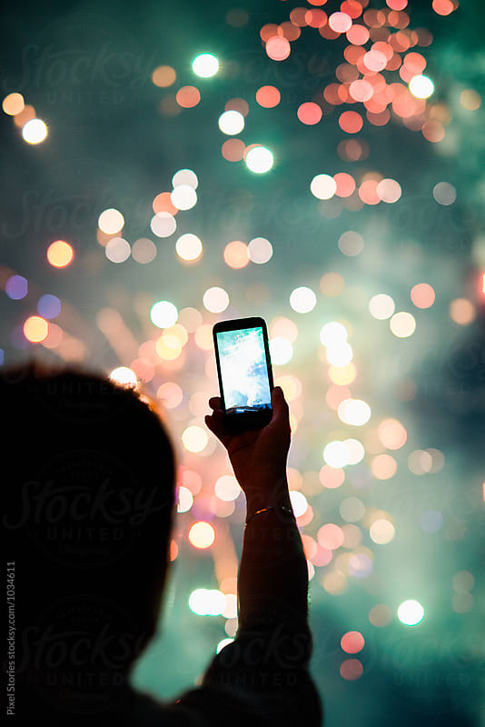 Person taking photos of fireworks using smartphone by Pixel Stories for Stocksy United