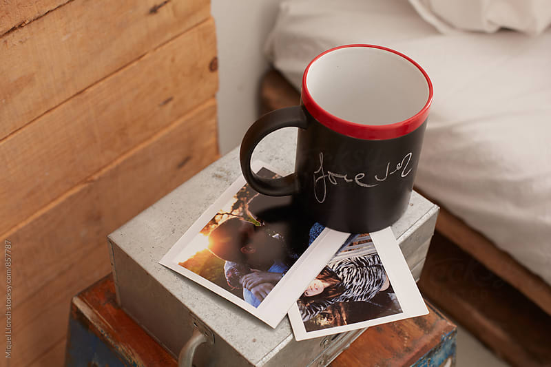 Close up of a mug on a table bedroom with the word forever written on it by Miquel Llonch for Stocksy United