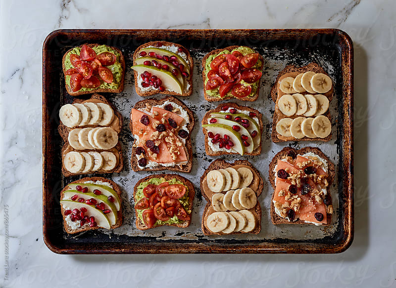 Assortment of breakfast toasts on baking tray for wellness by Trent Lanz for Stocksy United