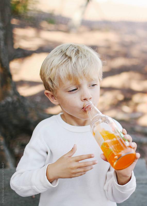 boy drinking a soda by Kelly Knox for Stocksy United