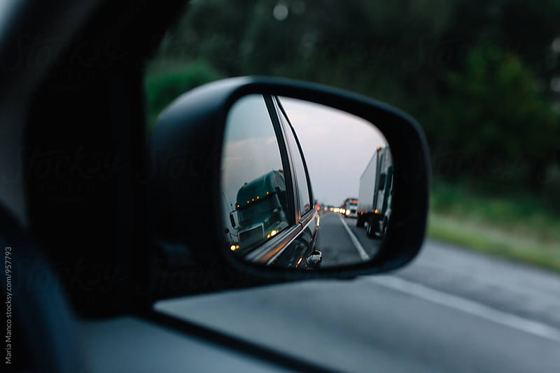 rear view mirror of trucks on highway by Maria Manco for Stocksy United