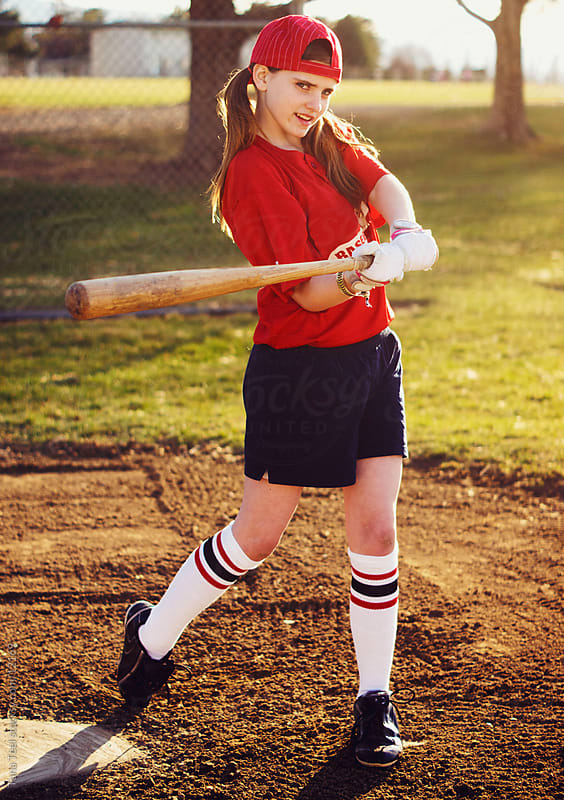 A young girl in retro baseball jersey swinging baseball bat.  by Tana Teel for Stocksy United
