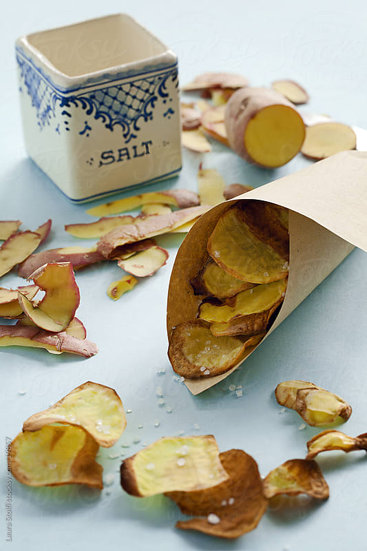 Homemade baked potatoes chips by Laura Stolfi for Stocksy United