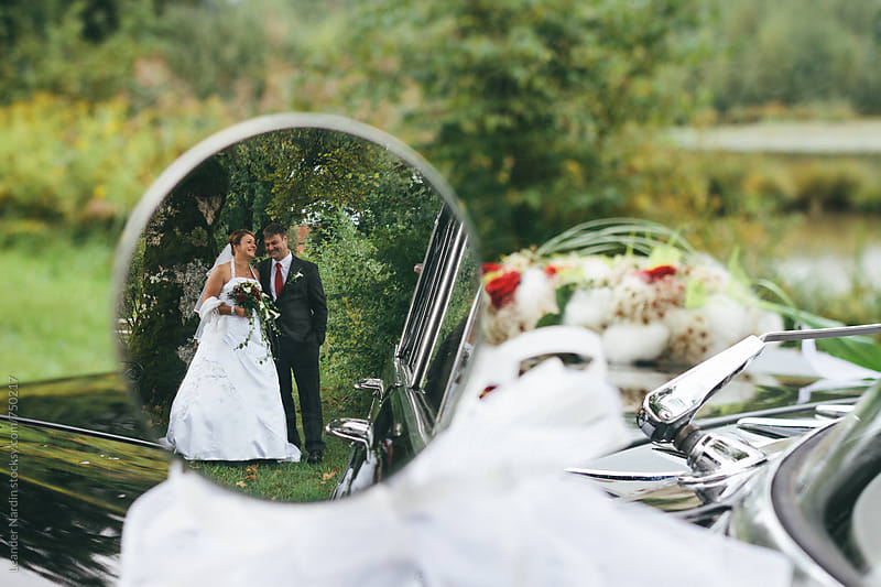 bridal couple seen in a rearview mirror from an classic oldtimer by Leander Nardin for Stocksy United