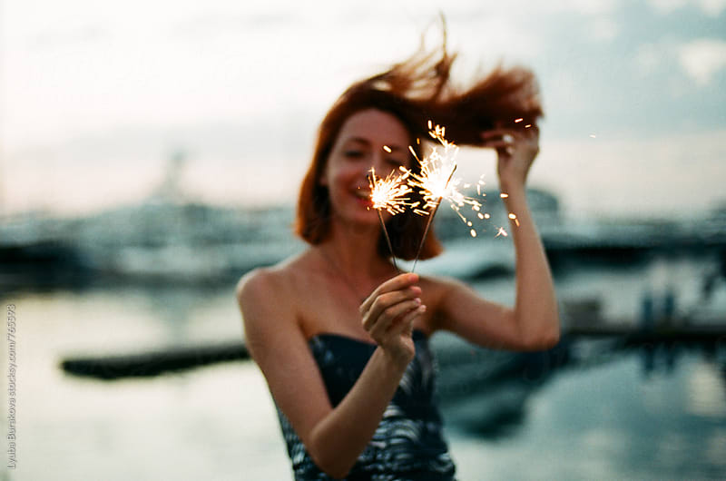 Woman holding a sparkler in front her face by Lyuba Burakova for Stocksy United