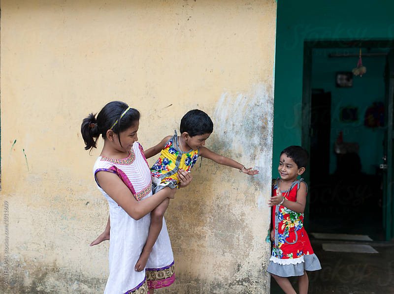 Twin girls and a teenage girl making fun and play by PARTHA PAL for Stocksy United