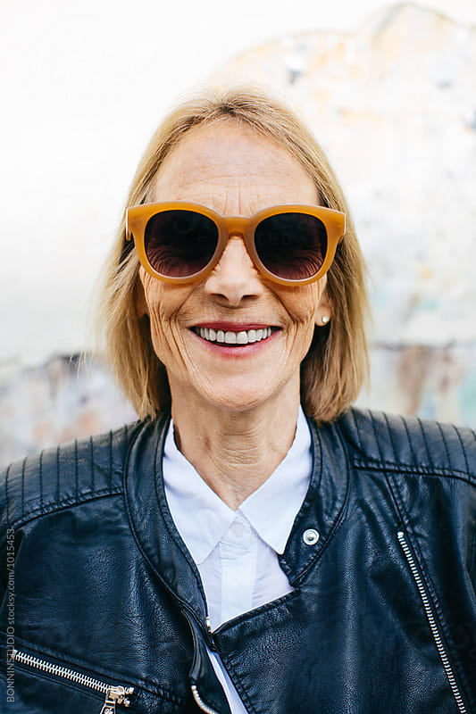 Portrait of a mature woman wearing a modern sunglasses.  by BONNINSTUDIO for Stocksy United