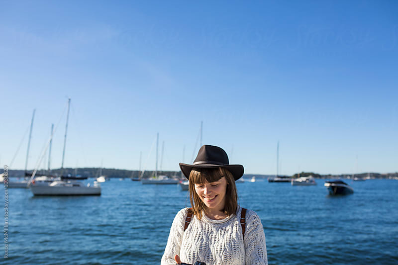 A girl stands in front of yachts in a Sydney cove by Reece McMillan for Stocksy United