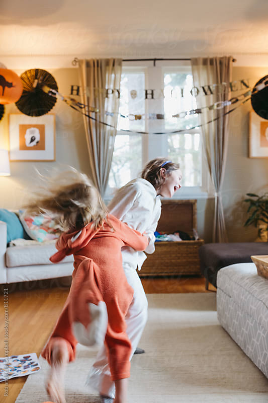 Young girls in halloween costumes dancing and jumping inside by Rob and Julia Campbell for Stocksy United