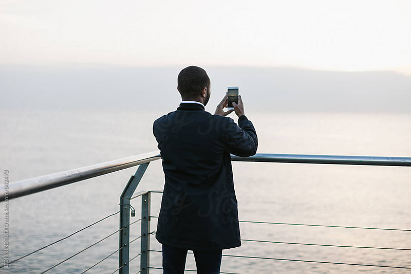 Back view of a man taking a photo of the sea. by BONNINSTUDIO for Stocksy United