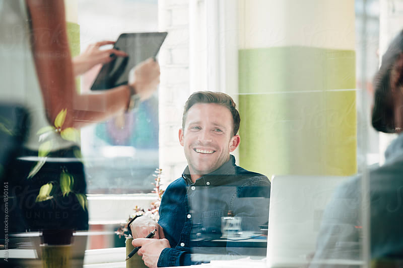Portrait of happy attractive businessman at meeting at work smiling by Aila Images for Stocksy United