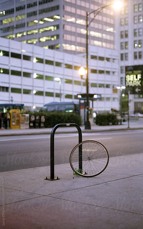 Bike wheel chained to a bike rack by Lucas Ottone for Stocksy United