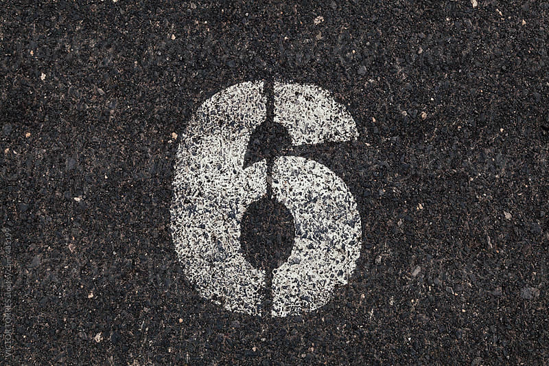 Number 6 Printed on White Over Dirty Asphalt by VICTOR TORRES for Stocksy United