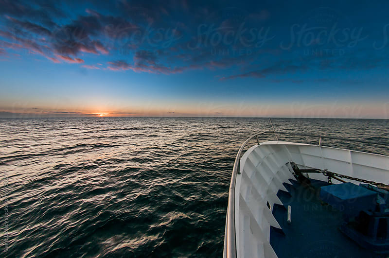 Boat Bow and sunset over ocean by Caine Delacy for Stocksy United