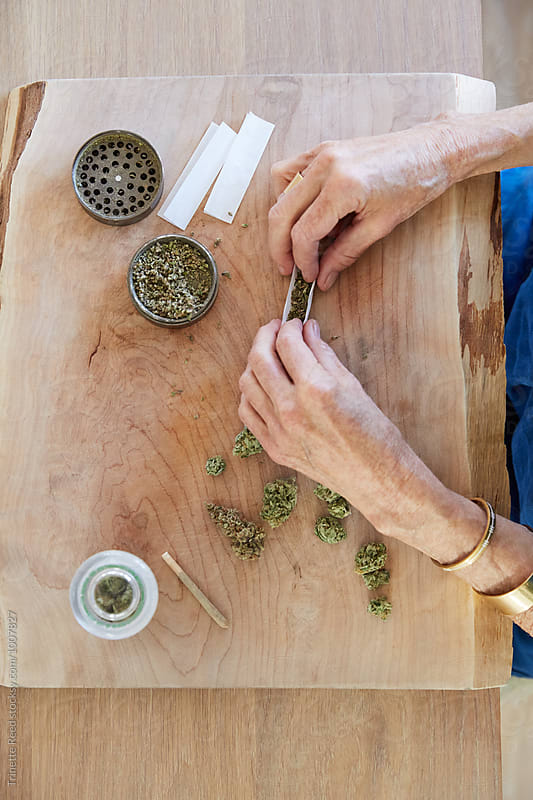 Senior woman's hands rolling a medical marijuana joint by Trinette Reed for Stocksy United