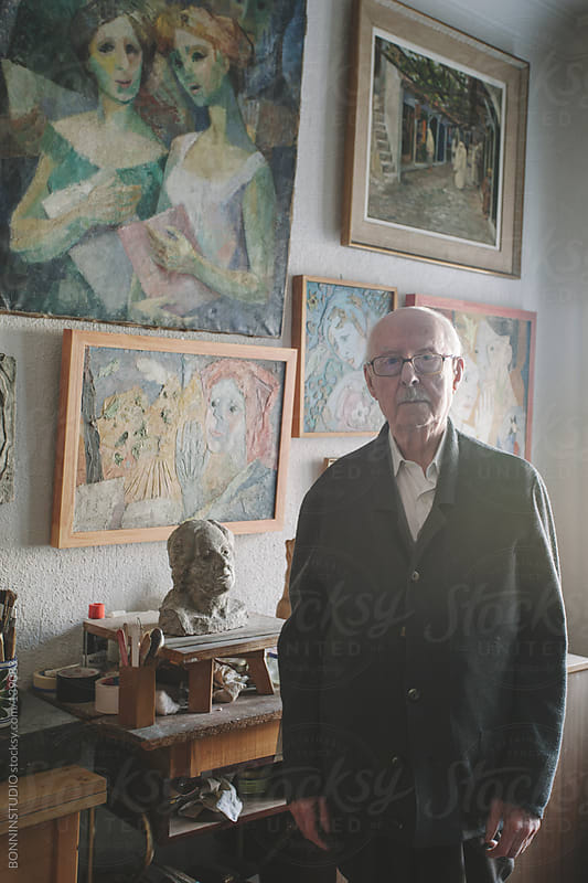 Portrait of old man standing in his studio of painting and sculpture. by BONNINSTUDIO for Stocksy United