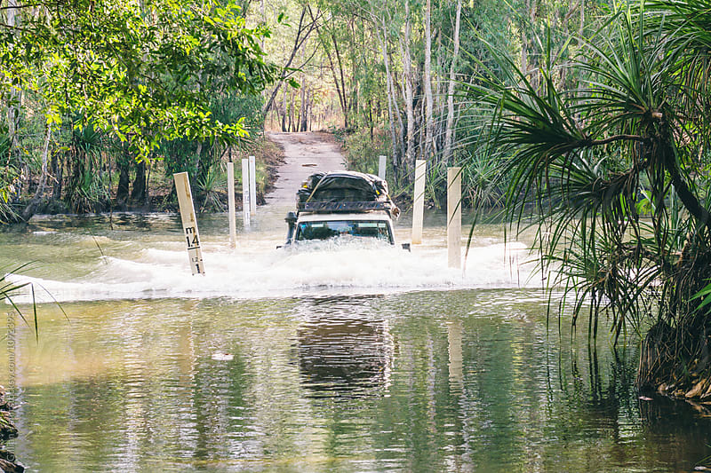 half submerged suv as it crosses a river by Gillian Vann for Stocksy United