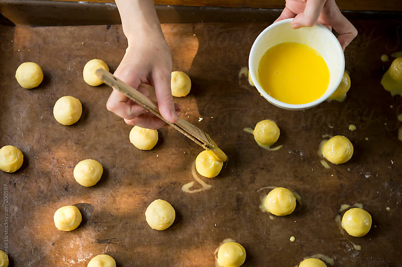Woman hands brushing egg yolk for baking bread by Lawren Lu for Stocksy United