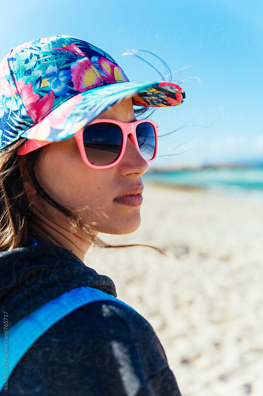 Fashion young woman wearing pink sunglasses and a colourful cap in a windy beach by Inuk Studio for Stocksy United