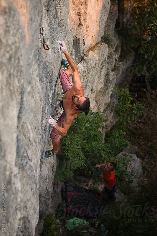 Strong man rock climbing a hard route outdoor at sunset by RG&B Images for Stocksy United