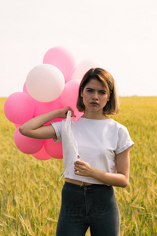 Serious teen girl with balloons looking at camera by Danil Nevsky for Stocksy United