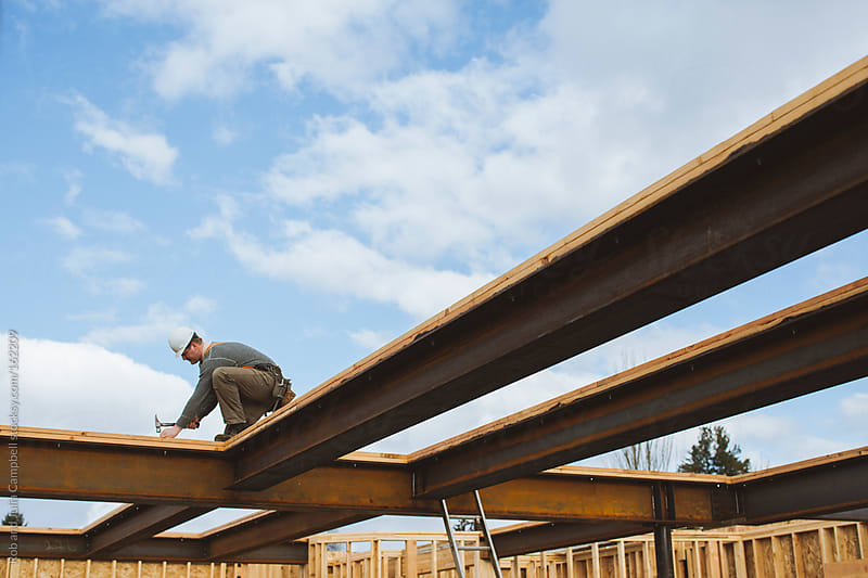 Carpenter man hammers board onto steel beams by Rob and Julia Campbell for Stocksy United