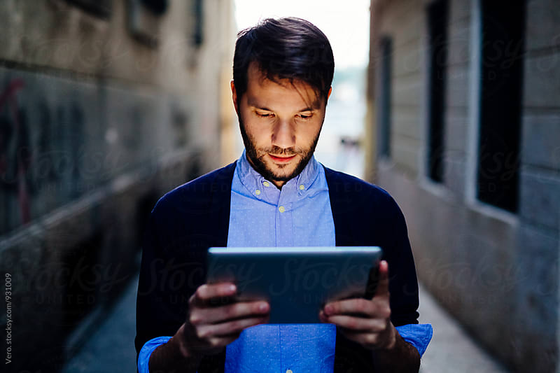 Man holding a digital tablet in a dark alley by Good Vibrations Images for Stocksy United
