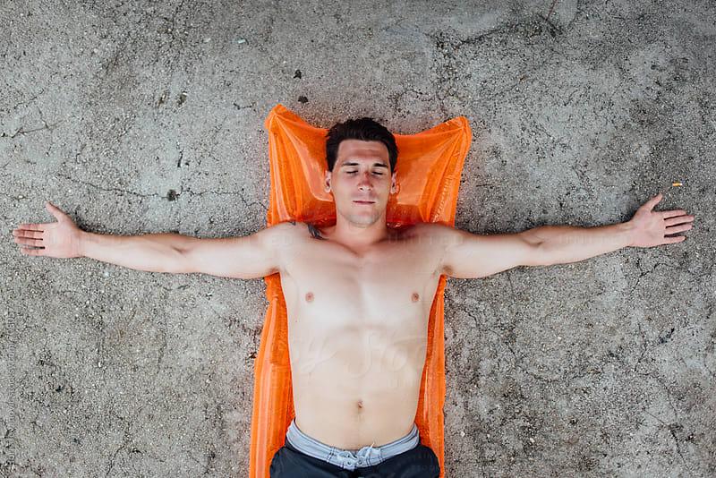 Attractive man sunbathing on the sea shore by Boris Jovanovic for Stocksy United