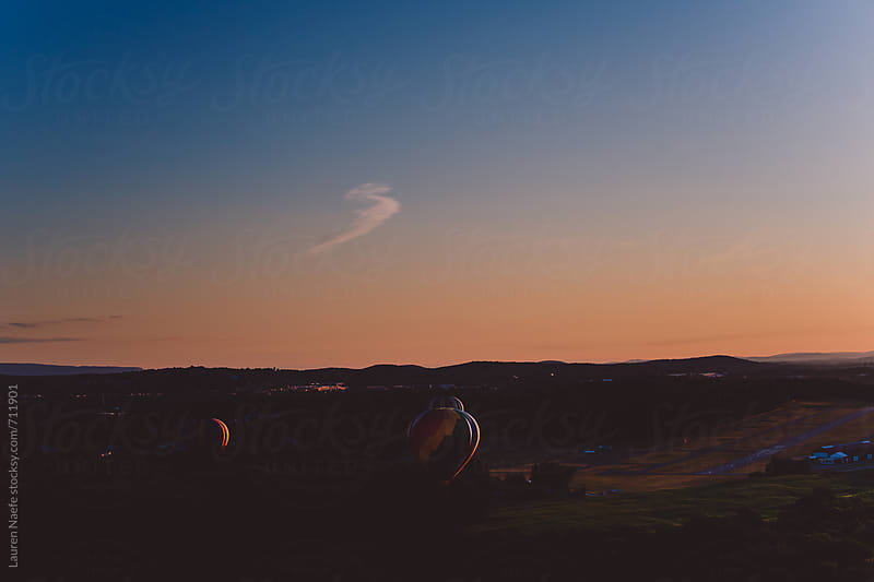 Hot air balloons flying at dawn by Lauren Naefe for Stocksy United