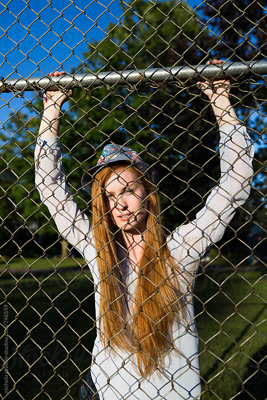 Portrait of a redhead girl through the fence by michela ravasio for Stocksy United