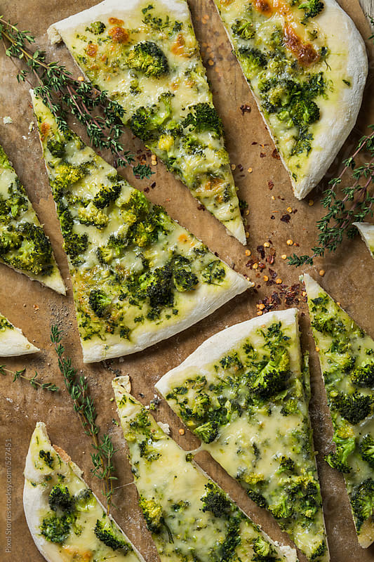 Food: slices of broccoli and cheese pizza by Pixel Stories for Stocksy United