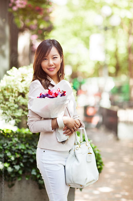 Beautiful happy Asian woman holding a bouquet of flowers by Suprijono Suharjoto for Stocksy United