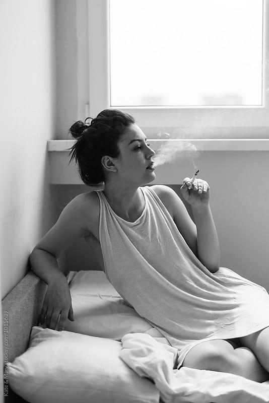 Portrait of beautiful woman who smoking cigarette by Kate & Mary for Stocksy United