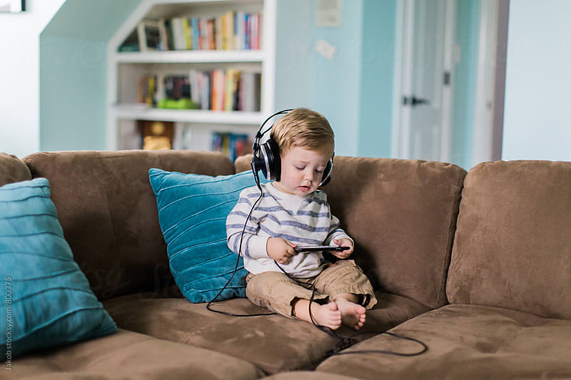 Cute young boy listening to music with big headphones by Jakob for Stocksy United