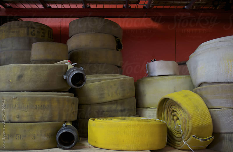 Rolled and Stacked Fire Hoses by Lucas Saugen for Stocksy United