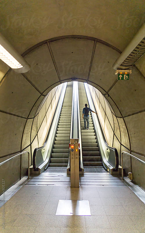 Man in a modern escalators by ACALU Studio for Stocksy United