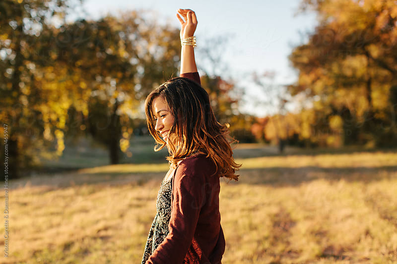Young woman dancing in an open field during sunset.  by Kristen Curette Hines for Stocksy United
