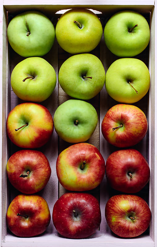 colorful apples in crate by Pixel Stories for Stocksy United