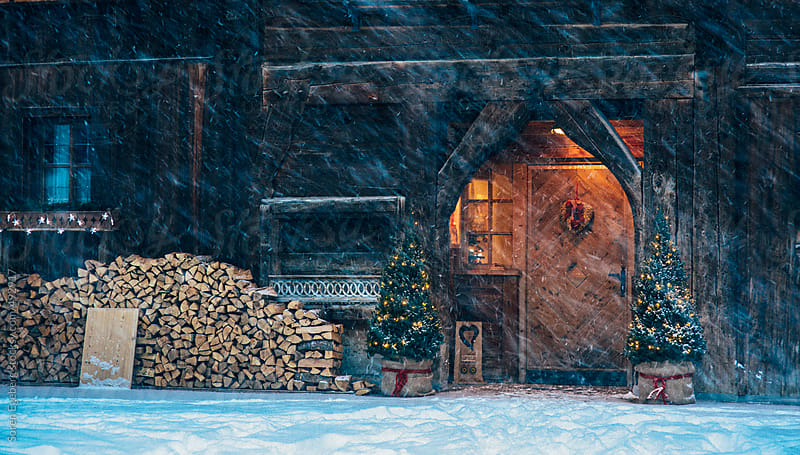 Old wooden house with christmas tree decorations outside and firewood in a snow storm in the mountains in winter by Soren Egeberg for Stocksy United