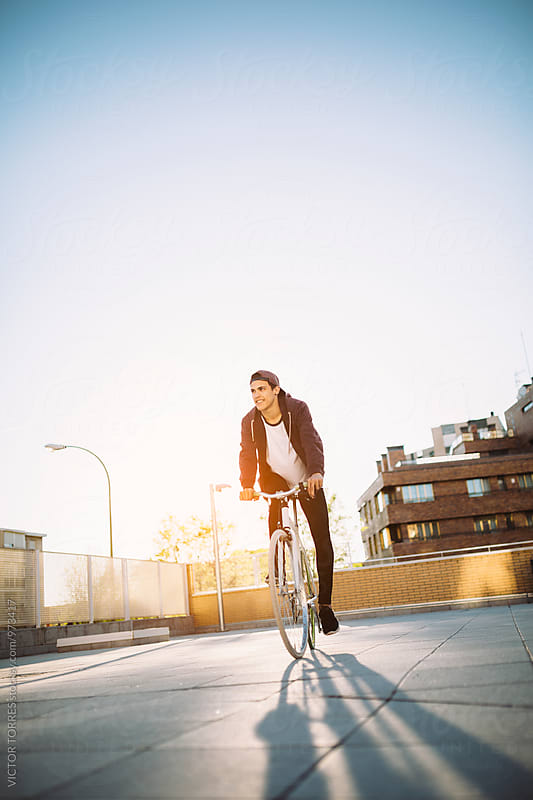 Teenager Riding a Bicycle at Sunset by VICTOR TORRES for Stocksy United