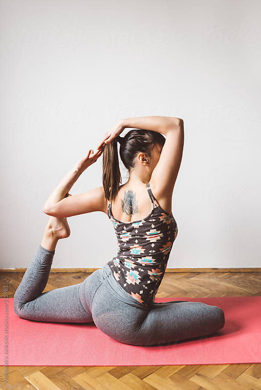 Young woman practicing yoga at home by Aleksandra Jankovic for Stocksy United