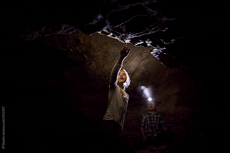 Girl and Boy Exploring A Dark Limestone Cave Underground by JP Danko for Stocksy United