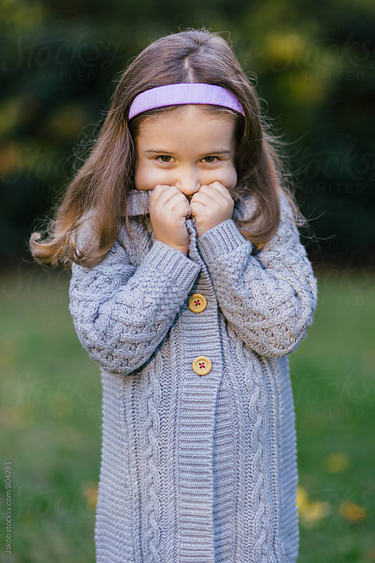 Cute young girl holding the collar of her cardigan by Jakob for Stocksy United