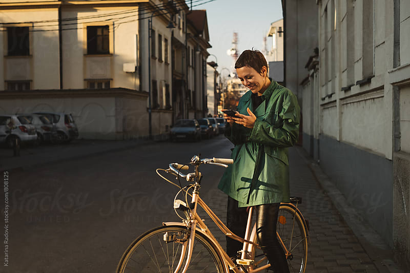 Pretty Woman Browsing on Her Phone While Sitting on a Bike by Katarina Radovic for Stocksy United
