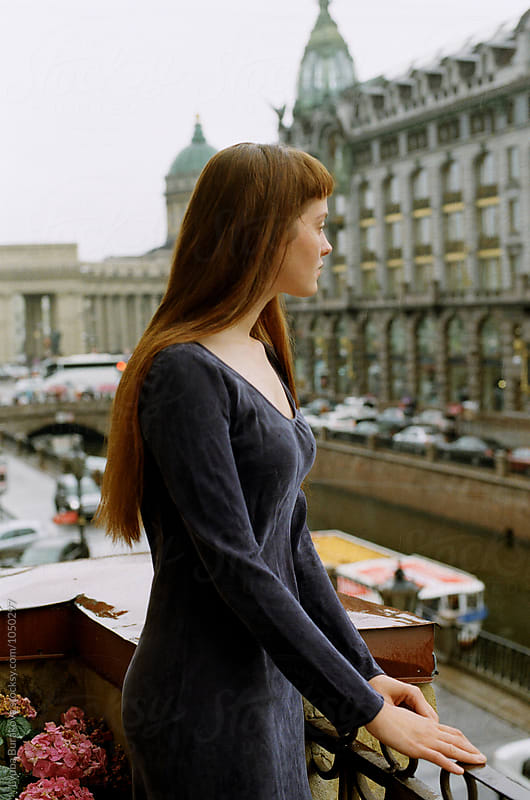 Young woman on a balcony looking away by Lyuba Burakova for Stocksy United