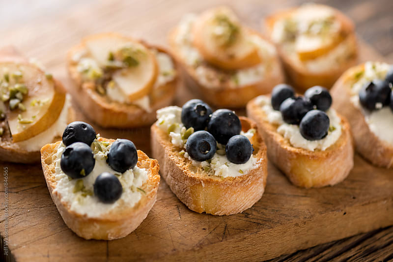 Crostini with Goats Cheese, Pear and Blueberry by Jeff Wasserman for Stocksy United